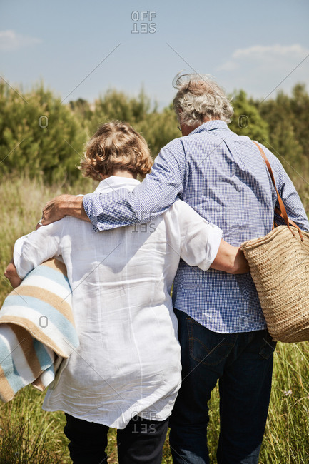 Couple with picnic basket and blanket going for picnic
