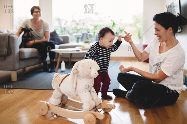 Woman looking at baby girl with rocking horse walking towards mother