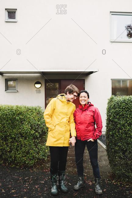 Smiling lesbian couple wearing raincoat standing outside house