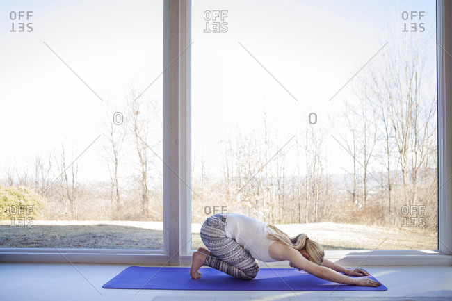 Side view of woman practicing yoga in downward facing dog position at home