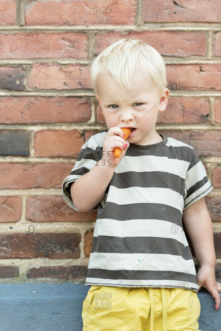 Boy eating carrot