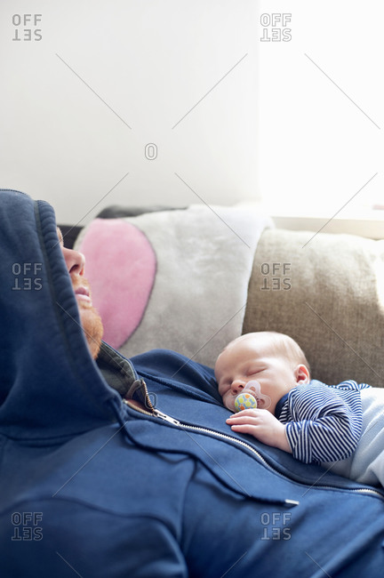 Father sleeping on sofa with baby son