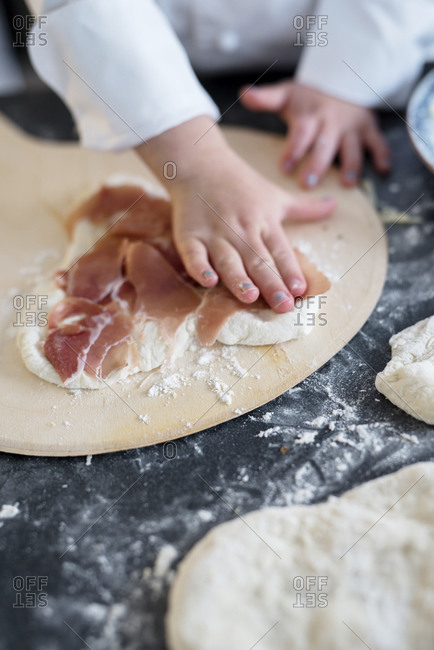 Child helping with making pizza