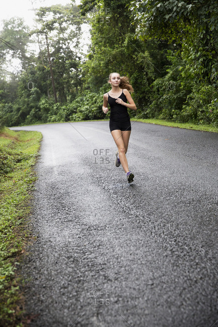 Teenage girl running on country road