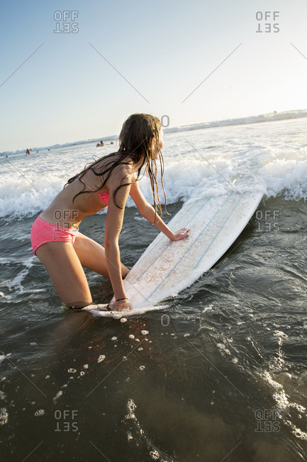 Young girl with surfboard in sea
