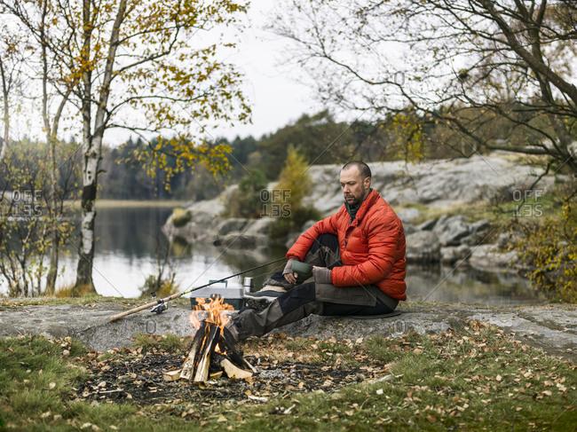 Mid-adult man sitting on lakeshore