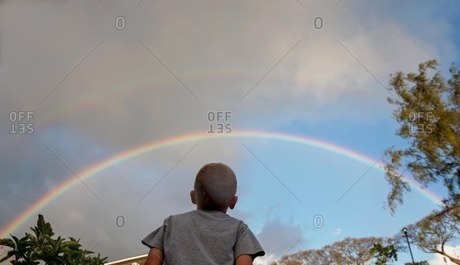 Low angle view of boy gazing at a rainbow