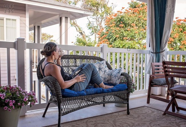 Woman drinking coffee on porch while reading tablet