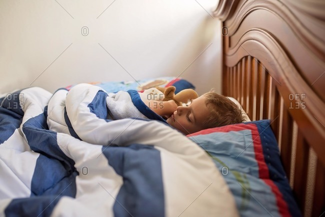 Boy with long eyelashes asleep in bed