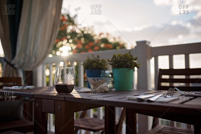 Glass of wine on outdoor dining table at sunset