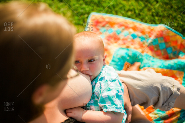 Mother breastfeeding her son outside on a blanket