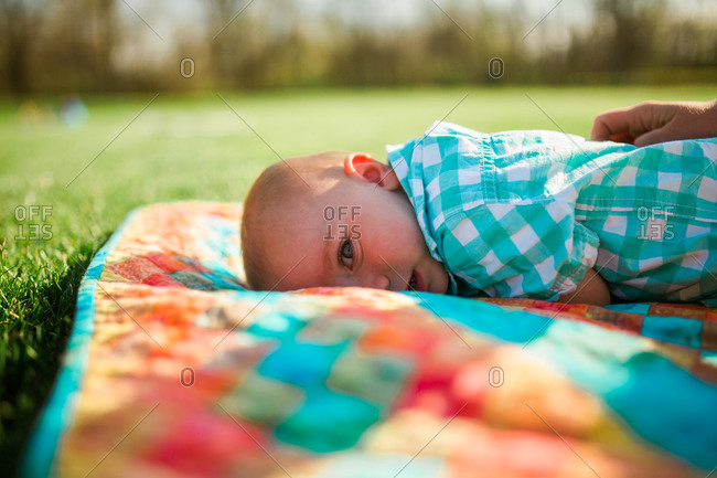 Young baby lying down on a blanket outside in a park