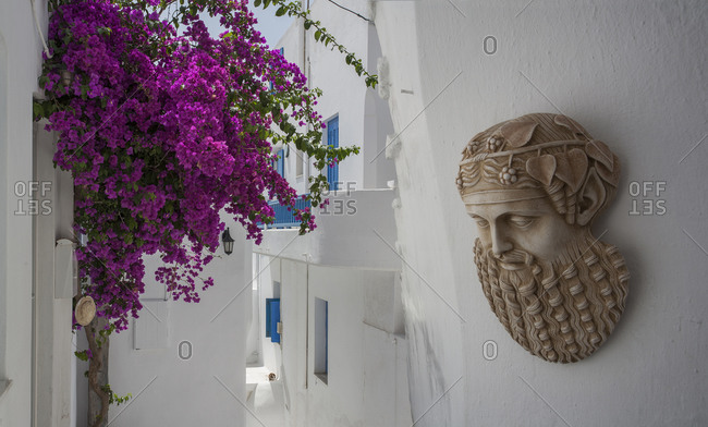 Sculpture and flowers on traditional building exterior