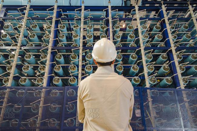 Hispanic technician examining power grid infrastructure