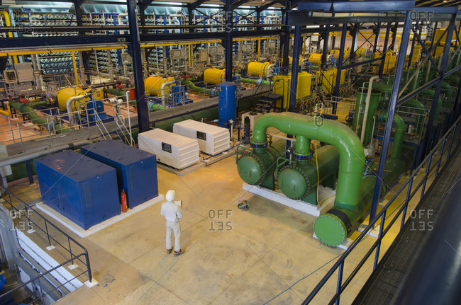 Hispanic technician supervising power plant
