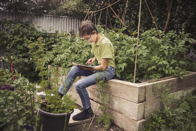 Mixed race boy using digital tablet in garden