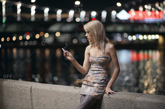 Caucasian woman smoking cigarette on urban bridge