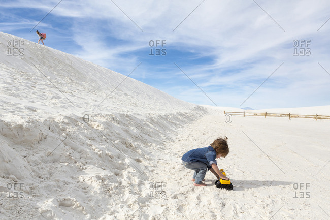 Caucasian boy playing with toy truck in desert