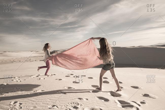 Caucasian children playing in desert