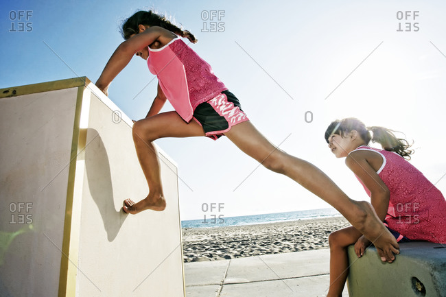 Girls climbing structure at beach