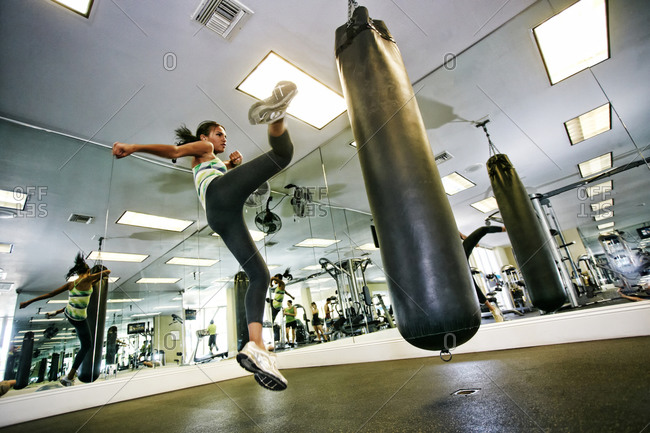 Mixed race woman kicking punching bag in gymnasium