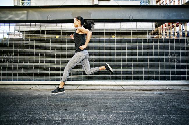 Mixed race athlete running on street