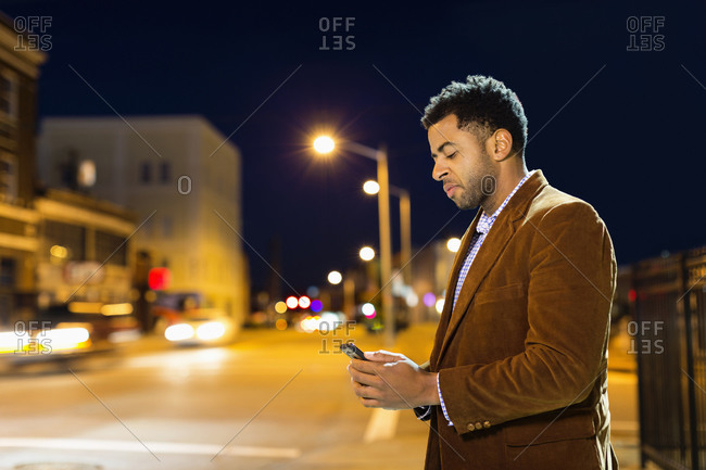 African American businessman using cell phone outdoors