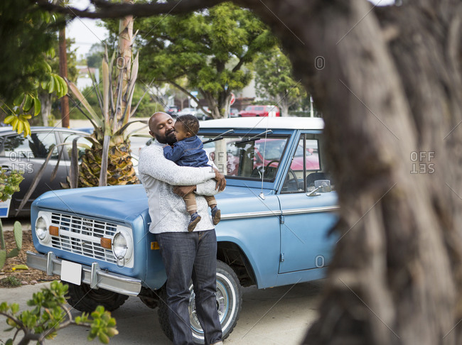 African American father holding son at truck