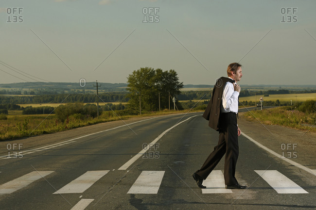 Caucasian businessman crossing rural street
