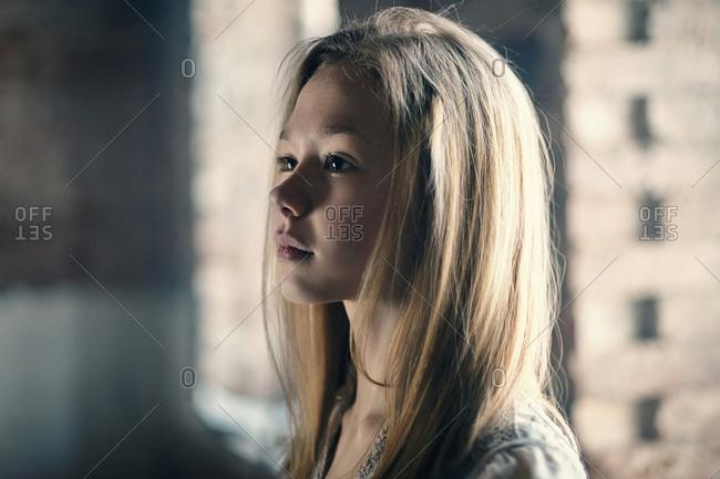 Caucasian girl standing at window