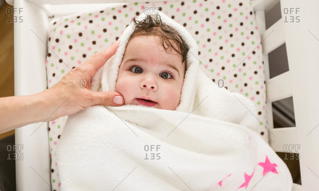 Baby wrapped in towel with pink stars