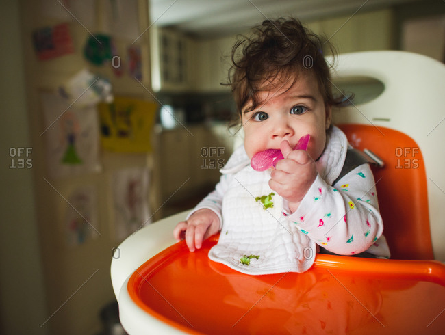 Baby girl sitting in high chair chewing on teething toy