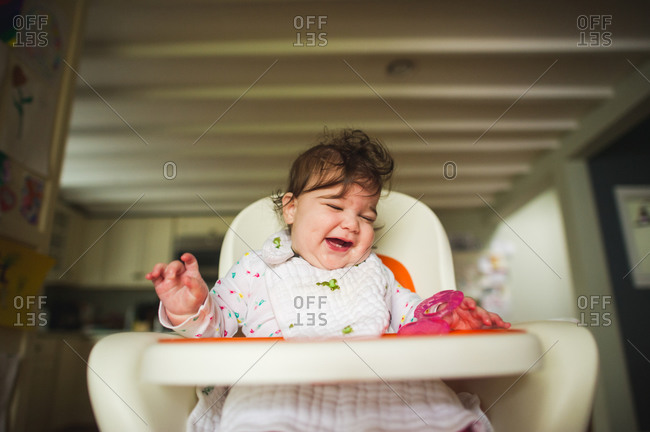Happy baby laughing in high chair