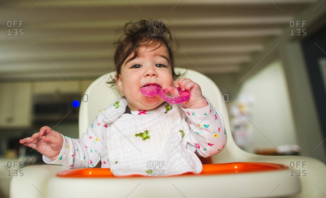 Infant with teething toy in mouth while sitting in high chair