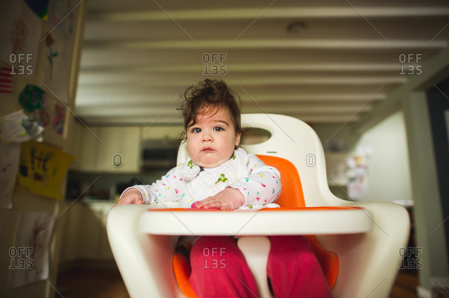 Infant girl sitting in high chair in kitchen