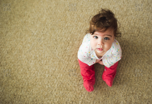 Baby girl in pink pants sitting on the carpeted floor