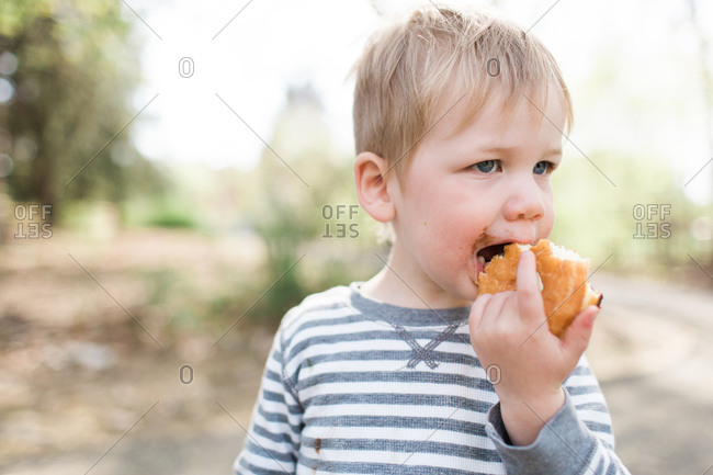 Boy taking a bit into a donut