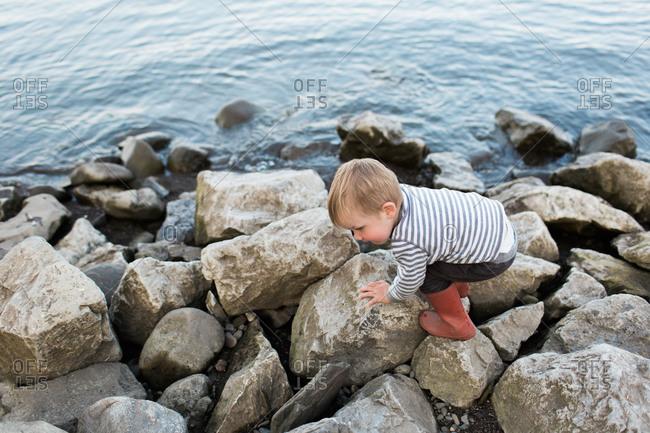 Boy in red rain boots walking on rocky shore