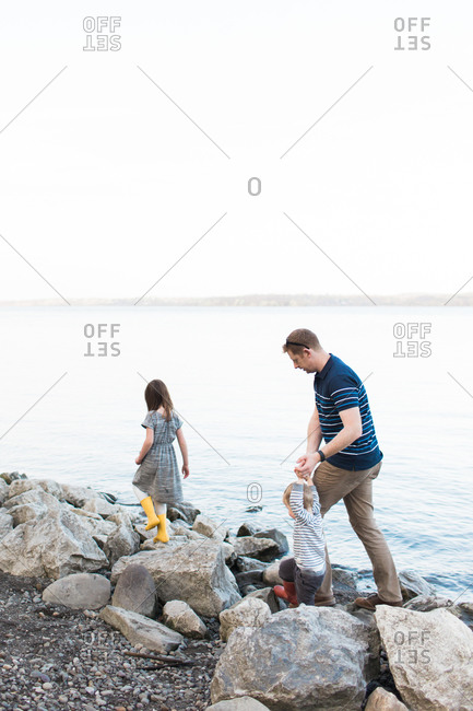 Father with daughter and son walking on rocky terrain along the shore