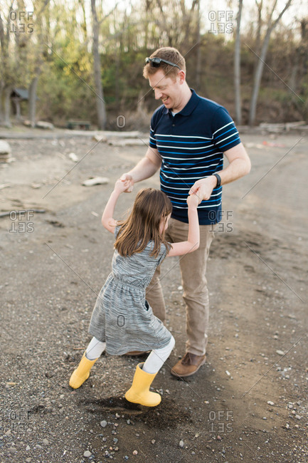 Dad and daughter holding hands dancing on dirt shore