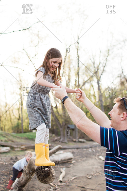 Girl preparing to jump off fallen tree with help of father