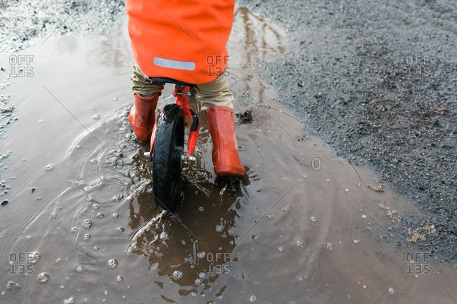 Kid riding bike through puddle wearing red rain boots