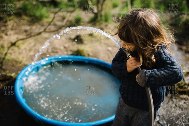 Young girl drinking from a garden hose outside