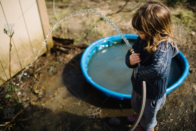 Young girl playing with a water hose outside