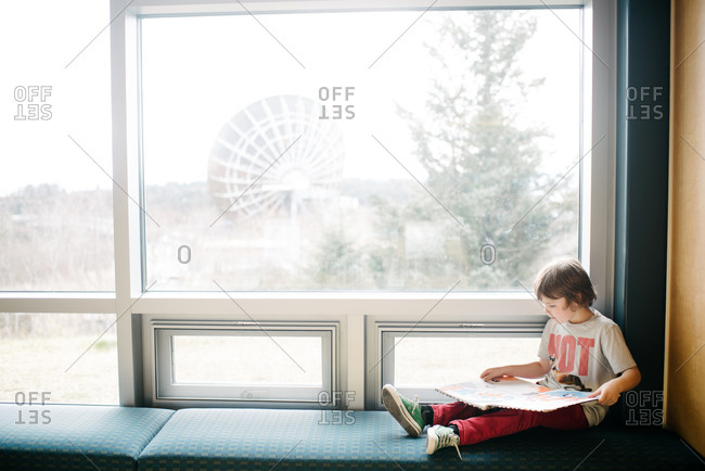 Young boy sitting on a bench near a window reading a book