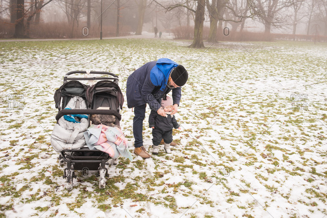 Father adjusts child's scarf in park with snow