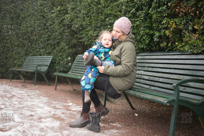 Woman comforts upset child on park bench