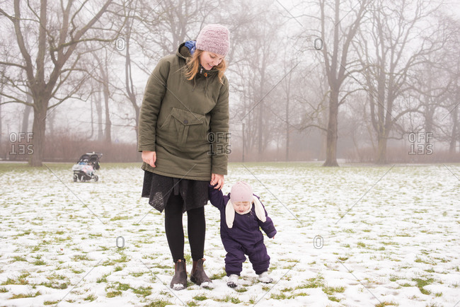 Mother holding toddler's hand in snowy grass