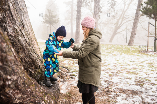Mother helps young child climb tree in park