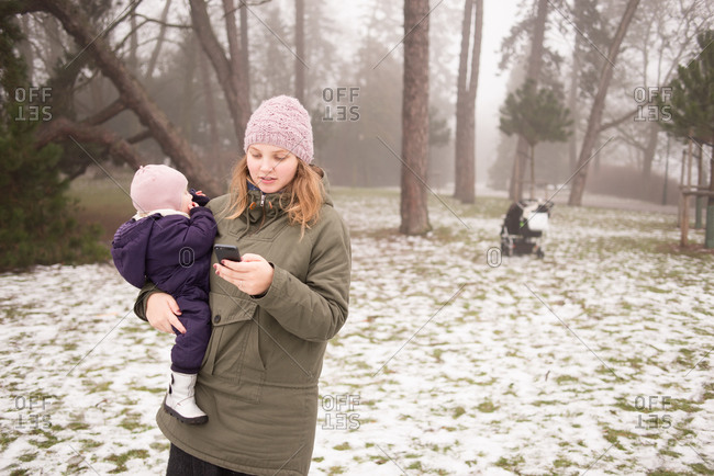 Woman holding baby in park checks smartphone